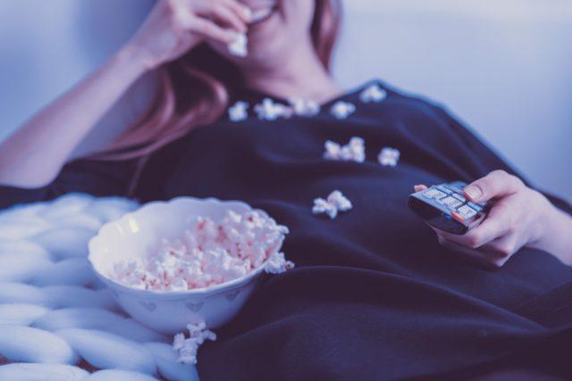 寝ながらポップコーンを食べて映画を見る女性