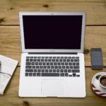 机の上のパソコンとコーヒーとノート